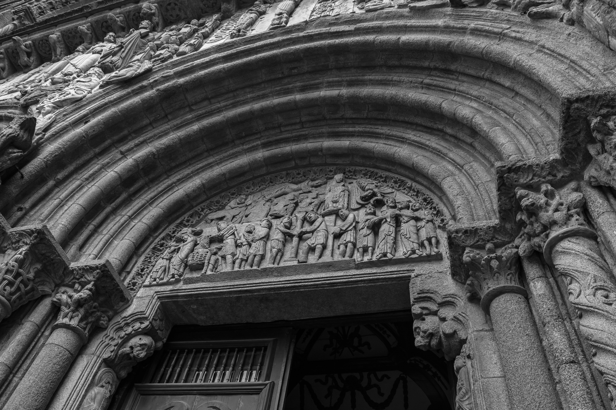 The facade of Platerías, southern door of the basilica, has two different entrances. <br>While the tympanum on the right-hand door shows several scenes of passion of Christ, such as judgment, entrapment, or flogging, the left tympanum symbolizes temptation, depicted in figures like the half-naked woman with a skull in her hands.<br> To the facade, which had to be rebuilt after a fire in the 13th century, figures were also added from the north door of the Cathedral.