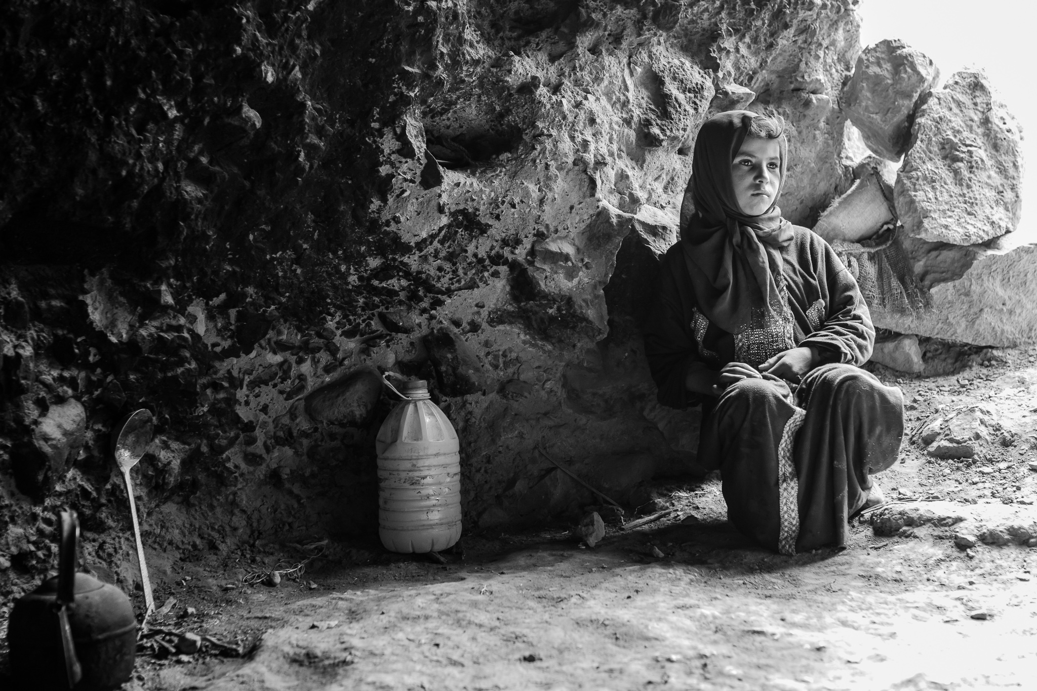 Bihya, sitting at the entrance of the cave where she will live with her family this summer. <br> The nomads usually sleep in one of the three caves they have, they normally use the other two for their flocks of sheep and goats and as a storage space for food and water.